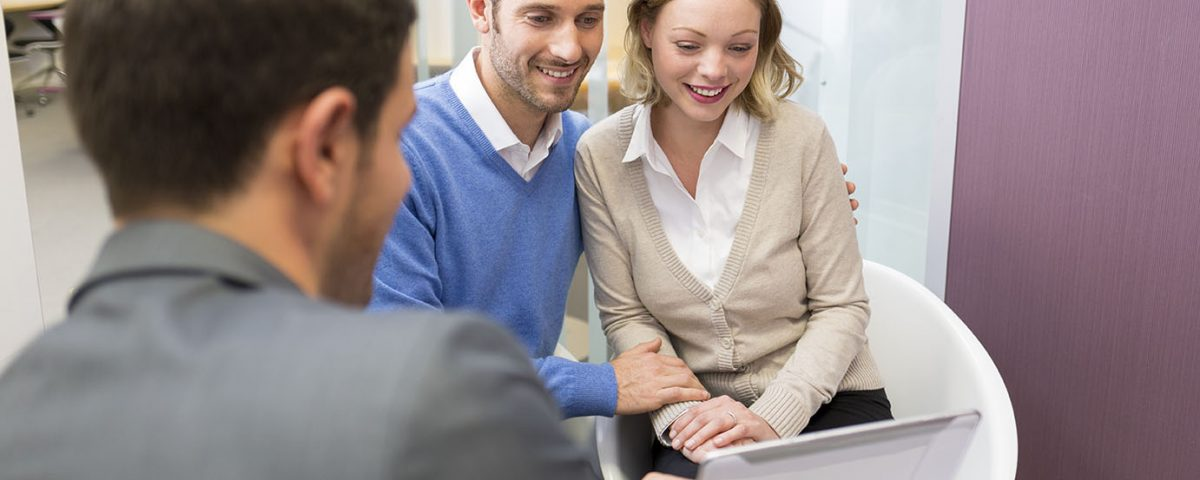 couple with broker calculating price for selling a business